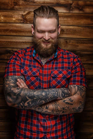 beefcake: Huge brutal man with beard and tattooes smiling
