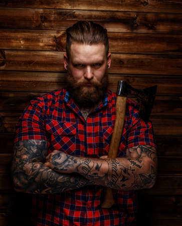 beefcake: Huge brutal man with beard and tattooes holding axe