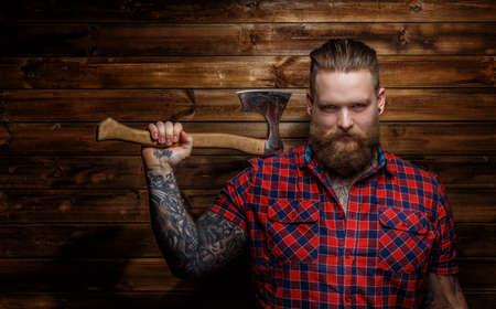 bigote: Hombre brutal enorme con barba y tatuajes sosteniendo el hacha Foto de archivo