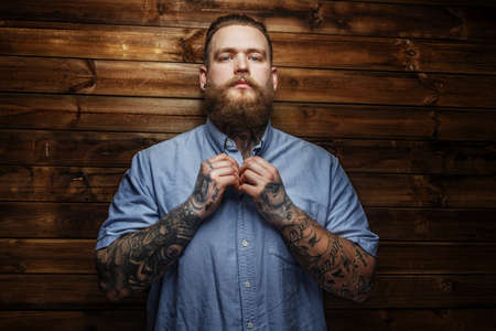 beefcake: Brutal male with beard and tatooes buttons up his t-shirt Stock Photo