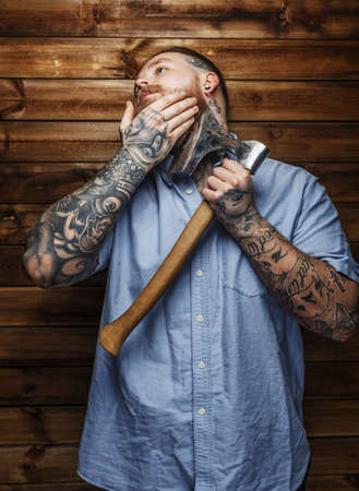 beefcake: Brutal huge male with tattooes shaves his beard with a big axe