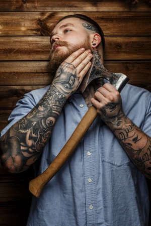 tattoed: Tattoed man in blue shirt and beard hold axe. Hand near face. Wooden background.