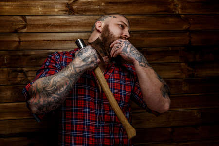 tattoed: Tattoed man in red shirt in a section with beard hang axe on wooden backgroud. One hand near man face.