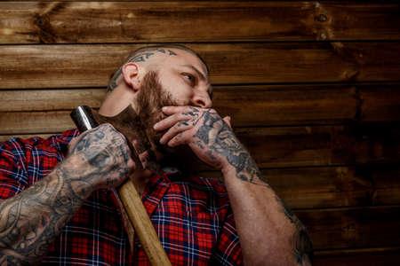 tattoed: Hombre tatuado en camisa roja en una secci�n con barba colgar el hacha en backgroud madera. Cara cerca de hombre con una mano. Foto de archivo