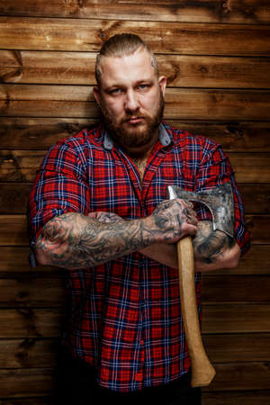 tattoed: Tattoed man in red shirt in a section with beard hang axe on wooden backgroud.