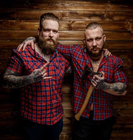 reb: Dos sirve tattoed con barba en camisa reb en unas secciones. Un hacha hombre espera. Fondo de madera.