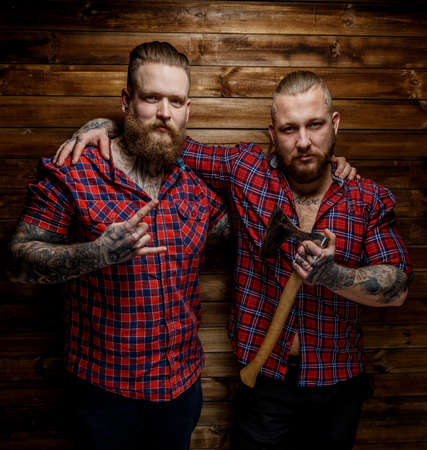 Two tattoed mans with beards in reb shirt in a sections. One man hold axe. Wooden background.
