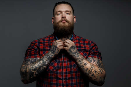 Tattoed man with beard, red shirt in a section,holds hands on a breast. Grey background.