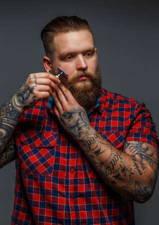 beefcake: Huge brutal man with tattoo shawing his beard with a razor Stock Photo
