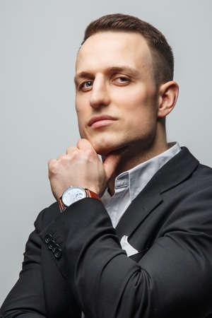 cheekbones: Portrait of handsome man in jacket with wrist watch on his hand Stock Photo