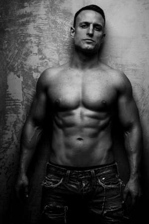 pectorals: Fashionable muscular guy poses showing his body Stock Photo