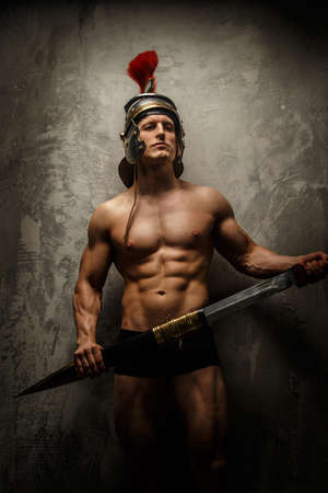 pectorals: Muscular warrior with sword and helmet posing in front of concrete wall