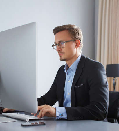 busy beard: Handsome young business man in a suit working with computer in office.