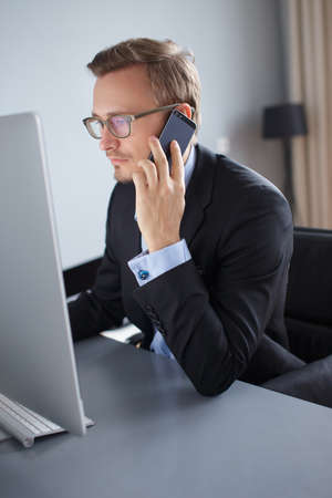 busy beard: Handsome young business man colling with mobile phone and working with computer in office.