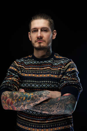 Portrait of man in color sweater and tattooes on his arms. Isolated on black.