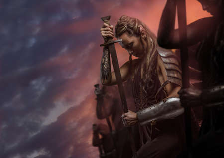 warfare: Beautiful female warrior elf with sword over cloudy sky Stock Photo