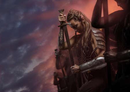 Beautiful female warrior elf with sword over cloudy sky Standard-Bild