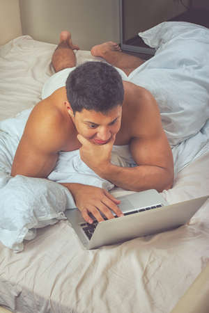 young man using a laptop at home photo