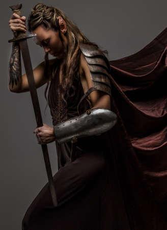 Portrai mystieke elf vrouw met zwaard, pantser en tatoeage op haar hand. Een zijaanzicht portraite. Stockfoto