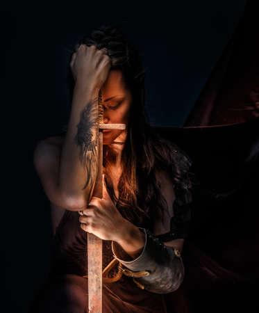 maquillaje de fantasia: Portrai de la mujer elfa mística con la espada, armadura y tatuaje en su mano.