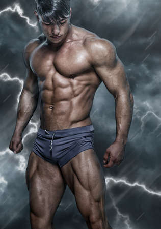 swimming trunks: Portraite of handsome, muscular, sexy man in grey swimming trunks on fusion-gray background. Stock Photo