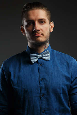 enticement: Portrait of a man in blue shirt with grey bow tie and tattooes on his hands. Isolated on black. Stock Photo