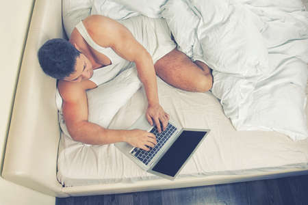 Young man using laptop at the bedtime photo