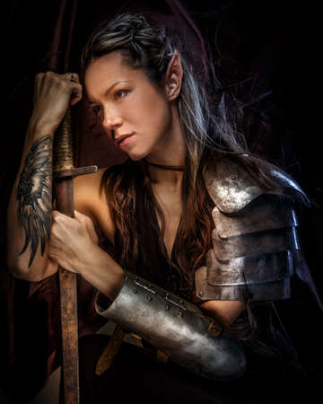 weapons: Portrai of mystic  elf woman with sword, armor and tattoo on her hand.