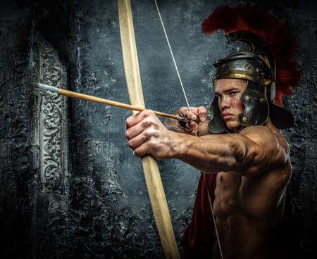 pectorals: Muscular man in Roman armor with bow. Stock Photo