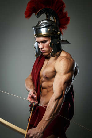 gladius: Wounded gladiator with bow isolated on grey. Stock Photo