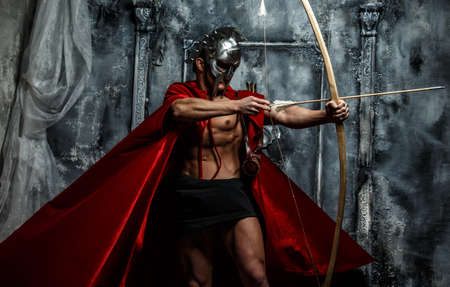 Wounded gladiator with bow isolated on grey. Stock Photo