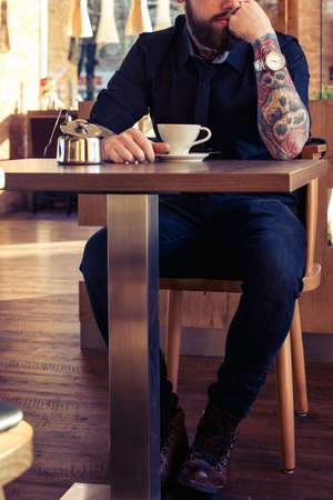 tattoo: Fashionable male with tattooes sitting at the table in coffee shop with a cup of coffee Stock Photo