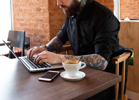 hombre rojo: Hombre serio con tatuajes que trabajan en un ordenador portátil en una cafetería