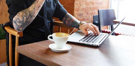 tattoed: Hombre tatuado que se sienta en una mesa con el ordenador port�til.