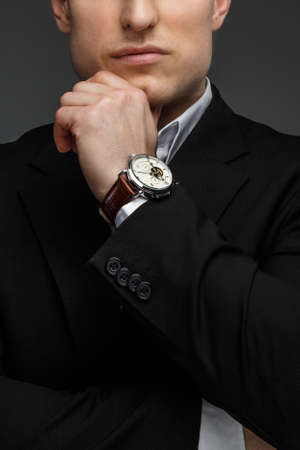 considerate: Half face portrait of successful business man in a black suit on grey background. Stock Photo