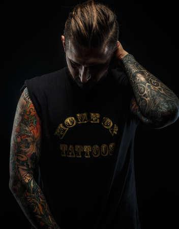 tatouage sexy: Portrait d'un homme en noir t-shirt et des tatouages. Sombre et des ombres profondes.