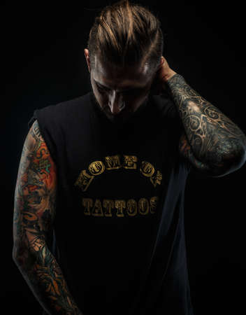 isolated on grey: Portrait of a man in black t shirt and tattoos. Dark and deep shadows.