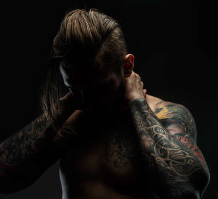 Portrait of a man with naked torso and tattooes. Dark and deep shadows.