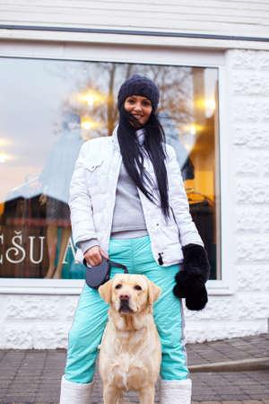 amigos abrazandose: Impresionante mujer con el pelo largo y negro en ropa de invierno possing con un perro. Foto de archivo