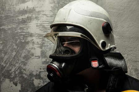 灰色背景: 灰色の背景の消防士ヘルメットと酸素マスクの男性 写真素材