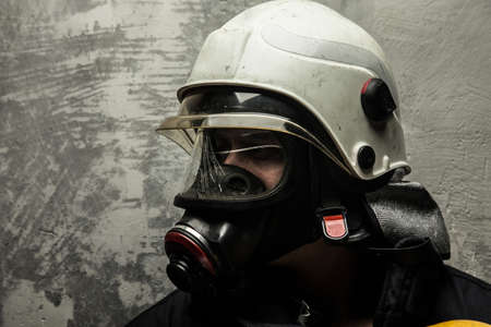 Male in oxygen mask and firefighter helmet on grey background photo