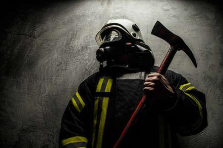 Brandweerman in uniform met bijl op een grijze achtergrond