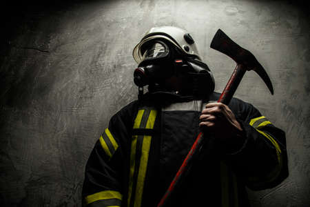 firemen: Firefighter in uniform with axe on grey background