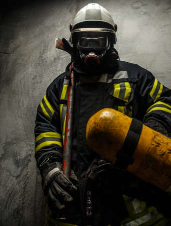 Firefighter in uniform with axe and oxygen on grey background photo