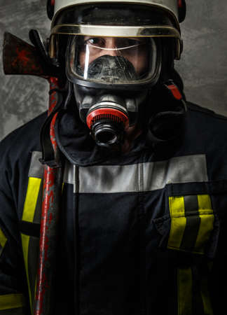 Firefighter in uniform with axe on grey background photo