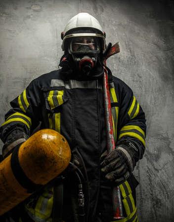 灰色背景: 斧と灰色の背景上の酸素と制服の消防士