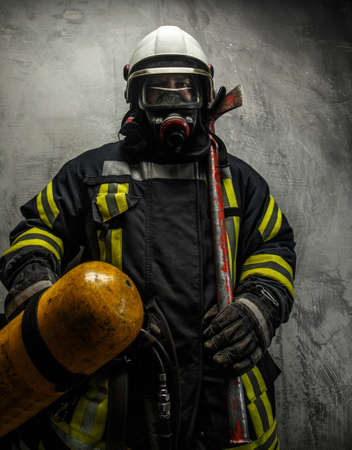 grey background: Firefighter in uniform with axe and oxygen on grey background