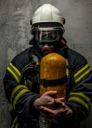 oxigeno: Bombero en uniforme con el hacha y el ox�geno en el fondo gris Foto de archivo
