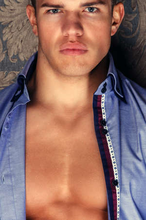 pectorals: Fashion portrait of muscular man in blue shirt.