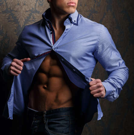 earnest: Fashion portrait of man in shirt showing his abs and poses over wall Stock Photo